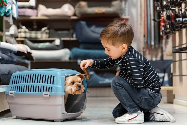 Kleine hond bij de dierenwinkel met eigenaar