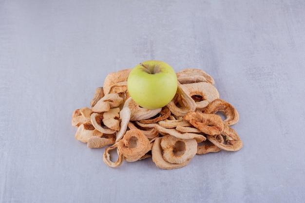 Kleine hoop gedroogde appelschijfjes met een hele appel bovenop op een witte achtergrond.