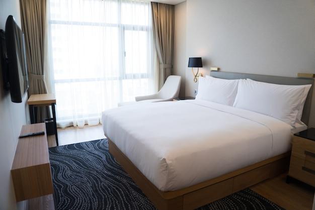 Kleine hotelslaapkamer met witte muren en panoramisch venster.