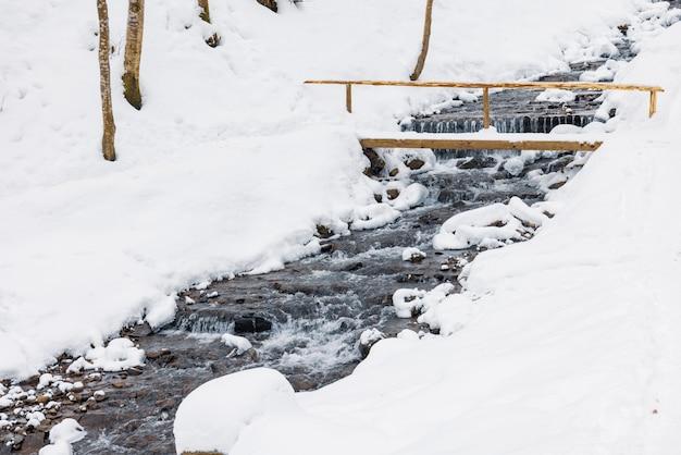 Kleine houten brug over een koude bergbeek in een winter forest-vallei