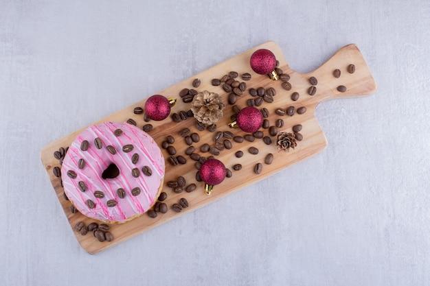 Kleine houten dienblad met donut, koffiebonen, dennenappels en kerstversiering op witte achtergrond.