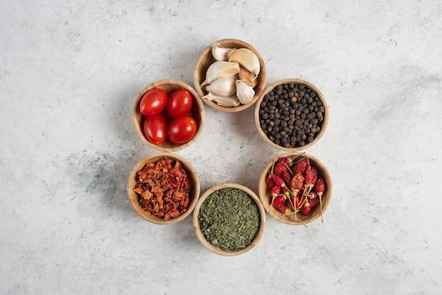Kleine houten kommen met kruiden en tomaten op marmeren achtergrond.