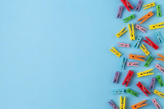 Kleine houten wasknijpers op heldere blauwe papier achtergrond