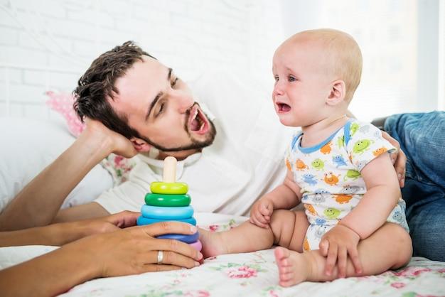 Kleine huilende jongen zit in de buurt van een rustgevende vader en speelgoed. het concept van kleine ondeugende kinderen.