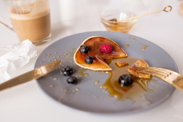 Kleine huisgemaakte pannenkoek met honing, frambozen en bramen die 's ochtends door iemand als ontbijt aan tafel wordt gegeten