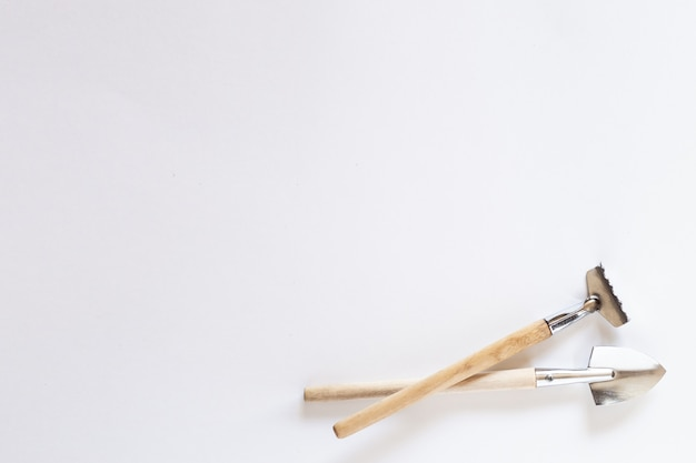 Kleine huishoudelijke schop, hark, hooivork op een witte achtergrond