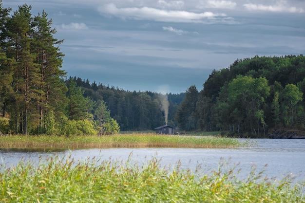 Kleine hut aan het meer in het noordelijke bos in de zomer