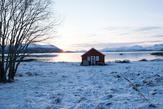 Kleine hut op de oever van de rivier, bedekt met sneeuw. winter dag