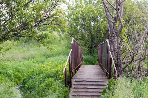 Kleine ijzeren brug met oude ijzeren wiel op het platteland