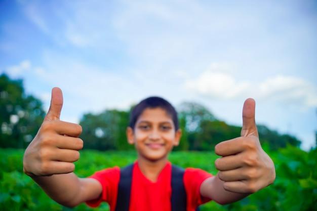Kleine indiase / aziatische jongen duimen opdagen, selectieve aandacht bij de hand