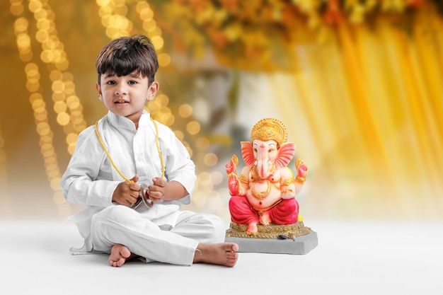 Kleine indiase jongen met lord ganesha, vieren ganesh festival