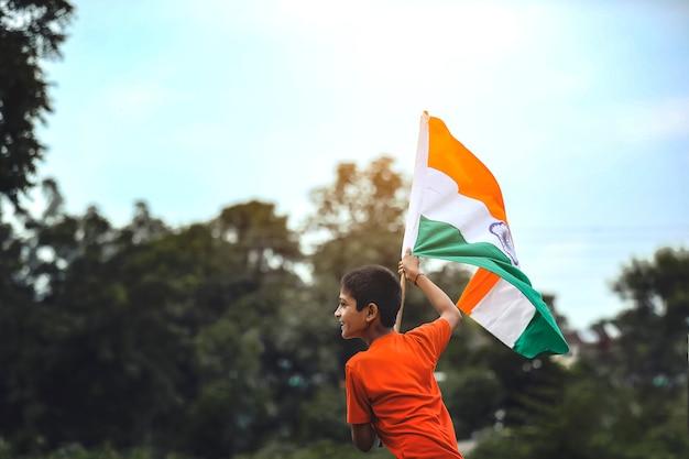 Kleine indiase kind houden, zwaaien of rennen met driekleurige vlag