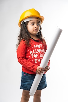 Kleine indiase meisjesingenieur met gele helm en tekenpapierrol of plan, geïsoleerd op witte achtergrond