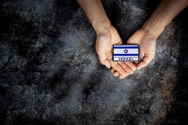 Kleine israëlische vlag in een hand. liefde, zorg, bescherm en veilig concept.