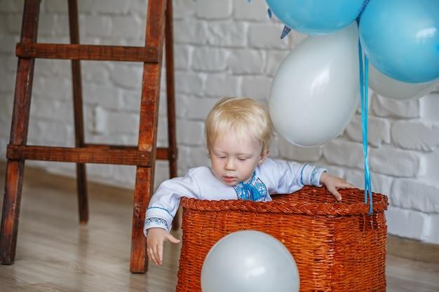 Kleine-jarige blonde jongen in traditioneel oekraïens geborduurd overhemd spelen met speelgoed in de ingerichte studio
