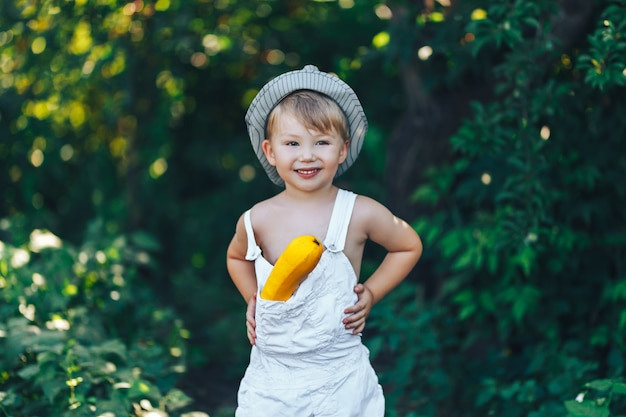 Kleine jong geitjelandbouwer die in witte kleren draagt die met gele pompoen, oogsttijd lachen