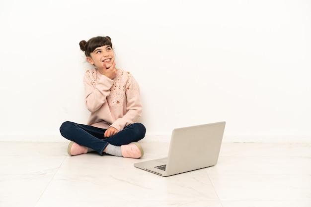Kleine jonge vrouw met een laptop zittend op de vloer naar de zijkant kijken en glimlachen