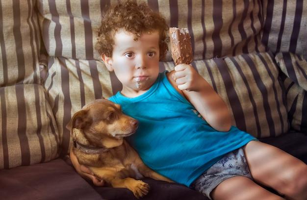 Kleine jongen, 4-5 jaar oud, blank, met een ijsje en zijn hondje zittend op de bank.