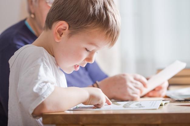 Kleine jongen 4 jaar oud leesboek. hij zit op een stoel in de zonnige woonkamer en kijkt naar foto's in een verhaal. kid huiswerk voor basisschool of kleuterschool. kinderen studeren.