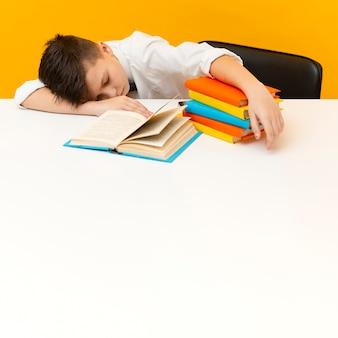 Kleine jongen aan een bureau met stapel boeken
