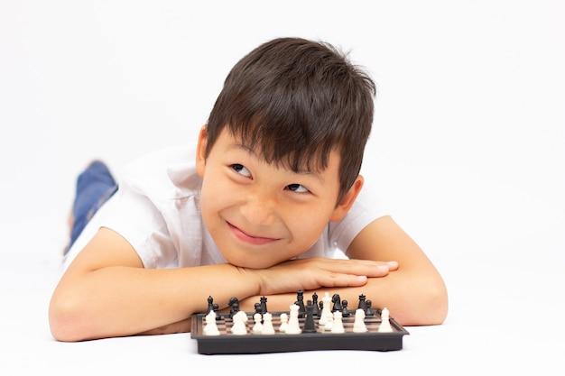 Kleine jongen aan het schaken op de grond