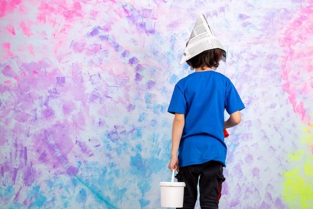Kleine jongen achteraanzicht in blauw t-shirt met kwast en verf op veelkleurige