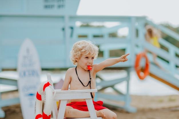 Kleine jongen als badmeester zittend op de strandwachtstoel op het strand