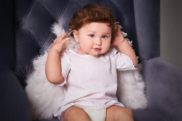 Kleine jongen als engel glimlach en zitten op luxe paarse fauteuil. peuter jongen in engelenvleugels in barokke stijl interieur kamer. internationale kinderdag.