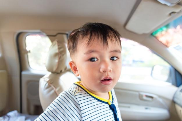 Kleine jongen azië die iets in veiligheidsauto zoekt voor reis.