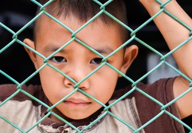 Kleine jongen azië triest achter de stal van toevlucht portret