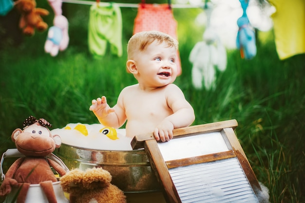 Kleine jongen badend in waskom