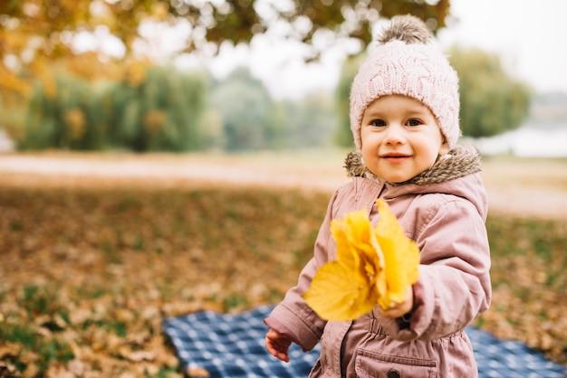 Kleine jongen bedrijf pack van bladeren in de herfst bos