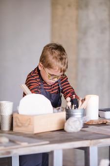 Kleine jongen beeldhouwt met interesse uit klei