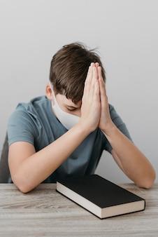 Kleine jongen bidden terwijl het dragen van een medisch masker
