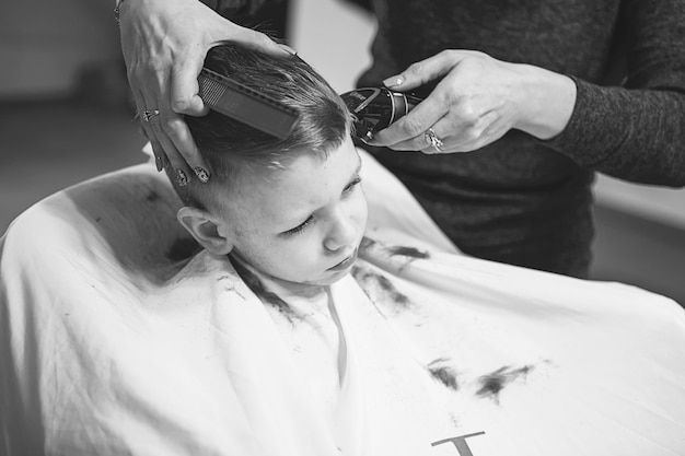 Kleine jongen bij de kapper. kind is bang voor kapsels. de handen van de kapper maken van kapsel aan kleine jongen, close-up. modieus kapsel voor jongens.