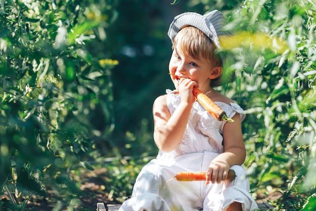 Kleine jongen boer kind zit in de rij van tomatenplanten, gekleed in witte casual overall pak en grijze hoed, wortel eten, oogsttijd