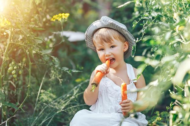 Kleine jongen boer kind zit in de rij van tomatenplanten, gekleed in witte casual overall pak en grijze hoed