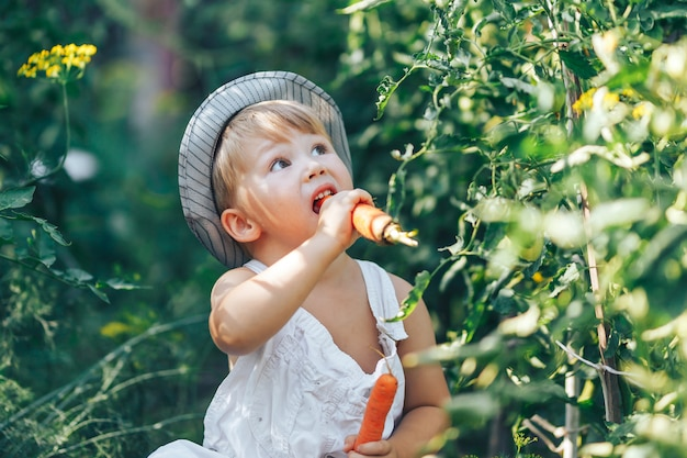Kleine jongen boer kind zit in de rij van tomatenplanten, gekleed in witte casual overall pak