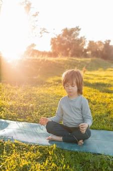 Kleine jongen buiten mediteren
