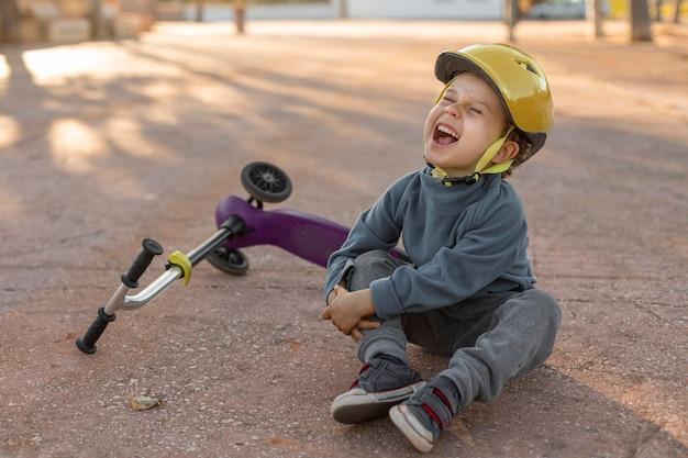 Kleine jongen buitenshuis gekwetst door het gevoel van een scooter