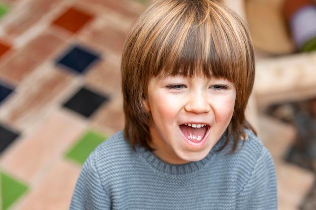 Kleine jongen buitenshuis glimlachen