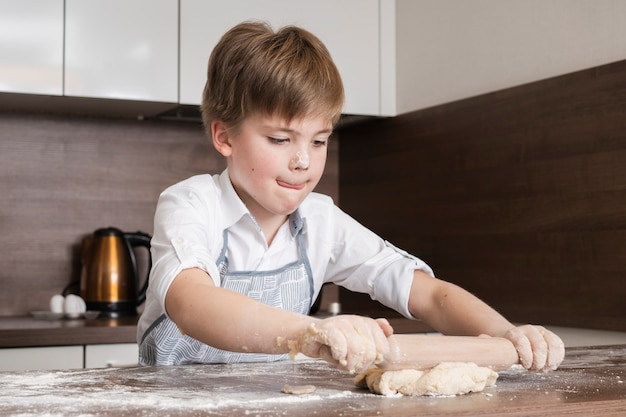 Kleine jongen concentraat om deeg te rollen