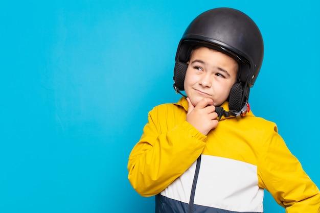 Kleine jongen denken expressie. motorhelm concept