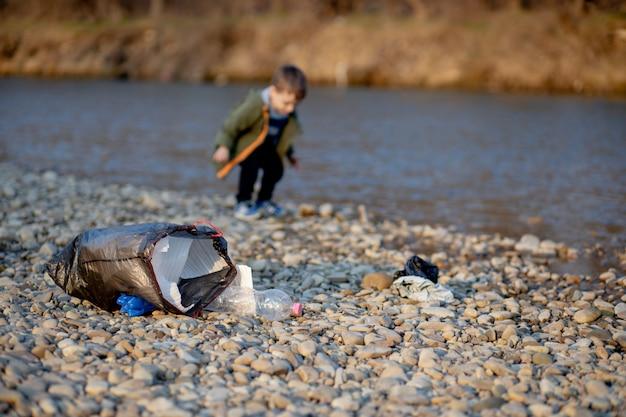 Kleine jongen die afval en plastic flessen op het strand verzamelt om in de prullenbak te dumpen