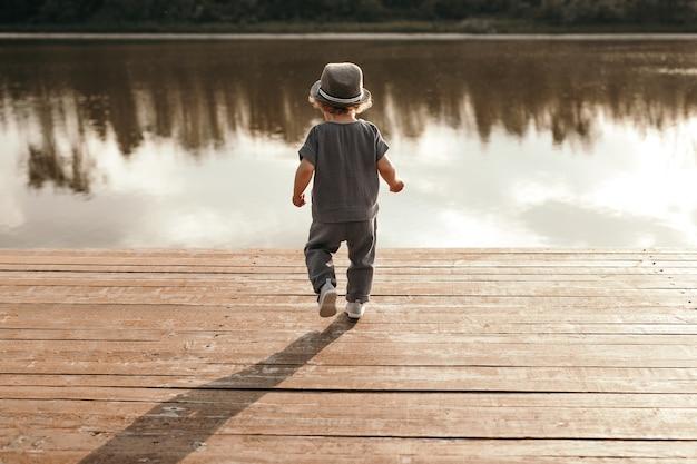 Kleine jongen die alleen naar het meer loopt