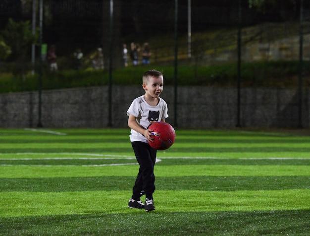 Kleine jongen die bal speelt op het voetbalveld, de avond en de schemering