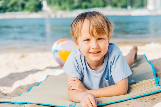 Kleine jongen die camera bekijkt en op strand glimlacht