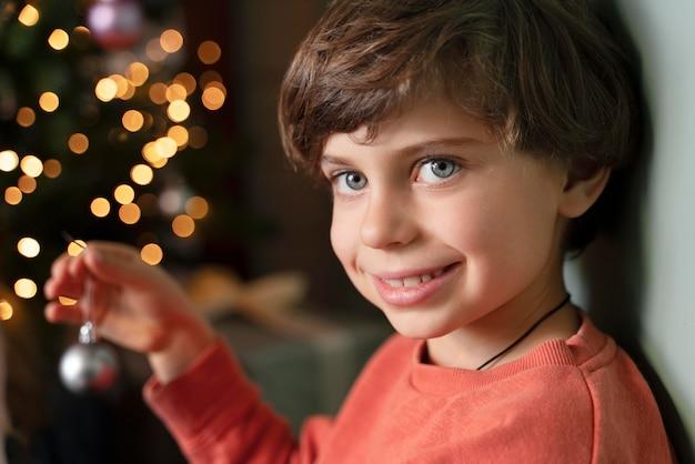 Kleine jongen die de kerstboom versiert