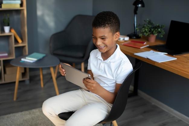 Kleine jongen die deelneemt aan een online les