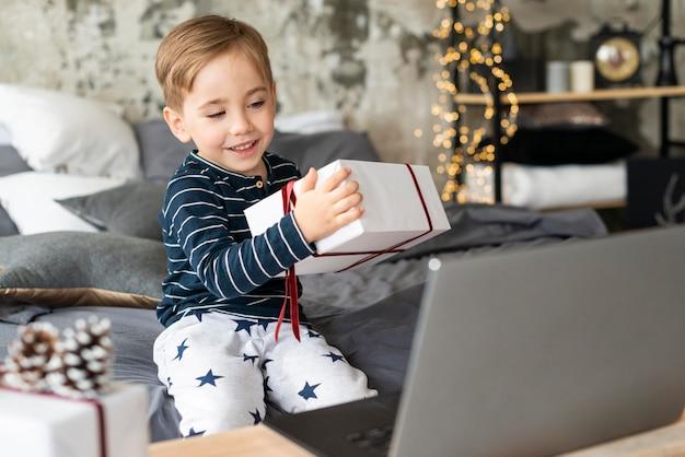 Kleine jongen die een cadeau houdt terwijl iemand video-oproepen